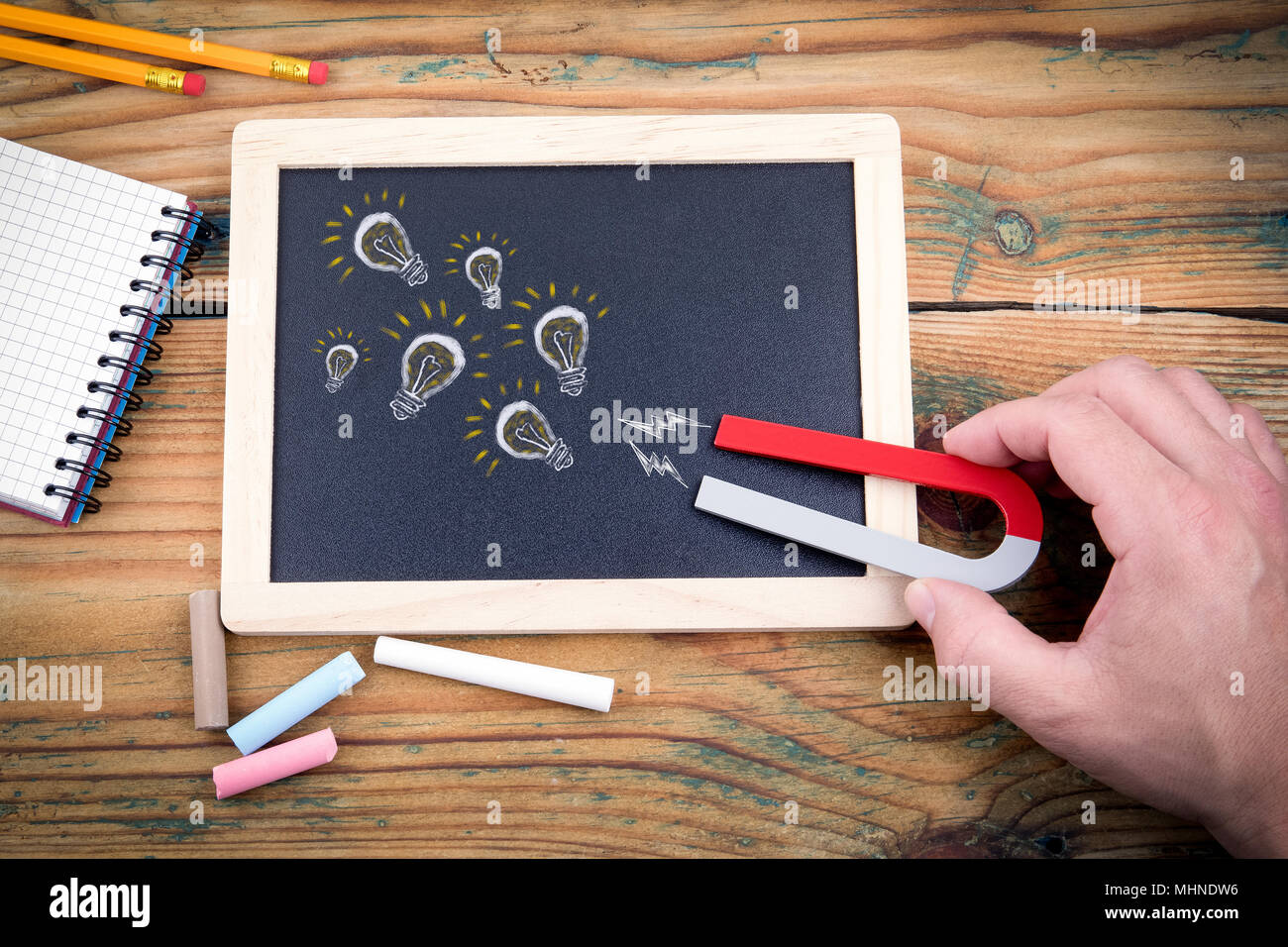 View of magnet attracting light bulb traffic of ideas, innovations, startups. Blackboard and chalk on wooden table - Stock Image