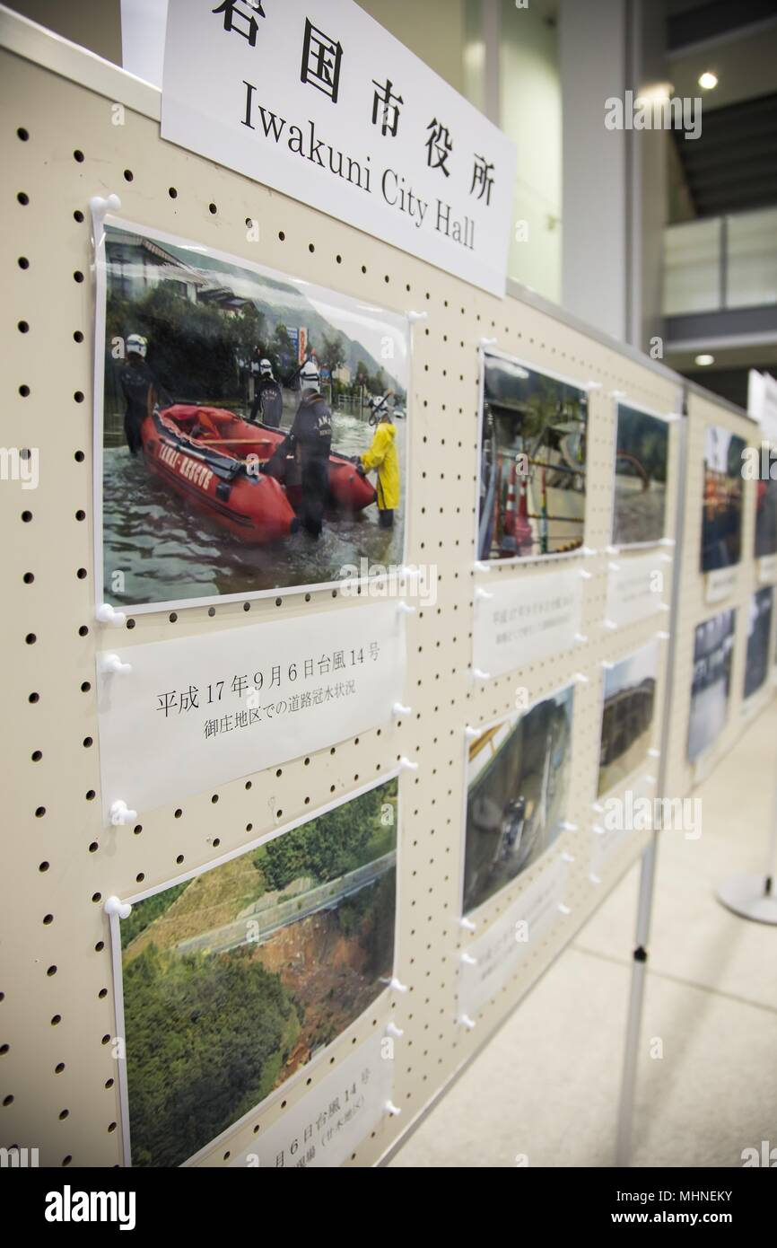A photo board is displayed in Iwakuni City, Japan, April 23, 2018, April 23, 2018. Each image depicts the relief efforts after the destruction of the Kyushu northern torrential rain, Hiroshima torrential rain, or the Kumamoto earthquake. It highlighted the efforts of the Japan Self-Defense Force, police departments, fire departments, volunteers and U.S. Forces Japan personnel involved in the restoration. (U.S. Marine Corps photo by Staff Sgt. William Faffler). () - Stock Image
