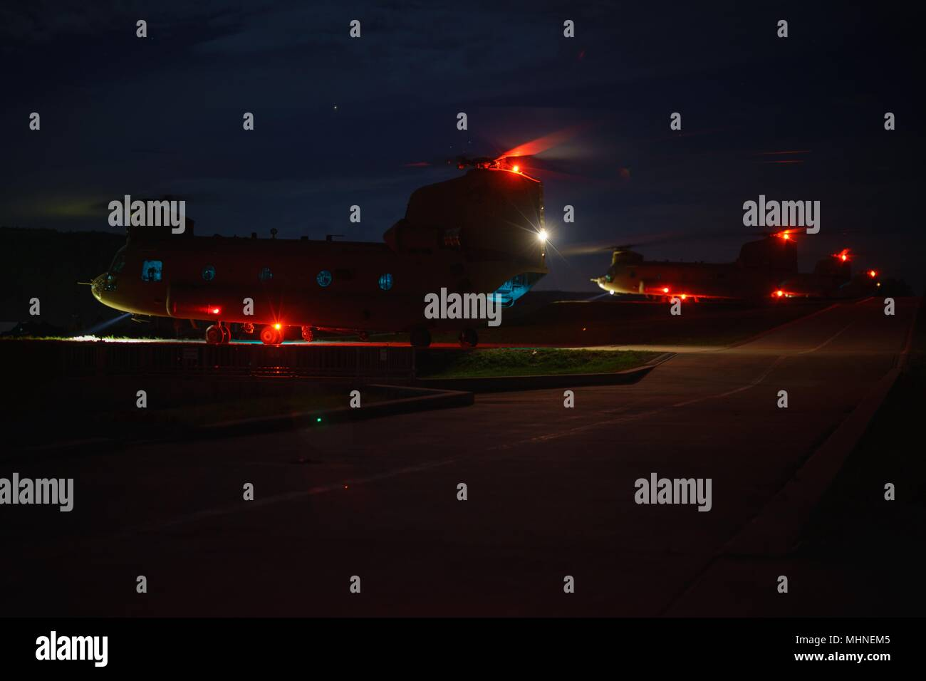 CH-47 Chinook helicopter flight crews of Company B, 2nd General Support Aviation Battalion, 227th Aviation Regiment, 1st Air Cavalry Brigade, 1st Cavalry Division, prepare for takeoff in support of a night assault training mission at Hohenfels Training Area, Germany, April 23, 2018, April 23, 2018. Soldiers of the battalion are providing aviation support during Joint Warfighting Assessment 18, an exercise that increases training readiness, future force development and interoperability with NATO allies. (U.S. Army photo by Sgt. Gregory T. Summers / 22nd Mobile Public Affairs Detachment) Image c - Stock Image