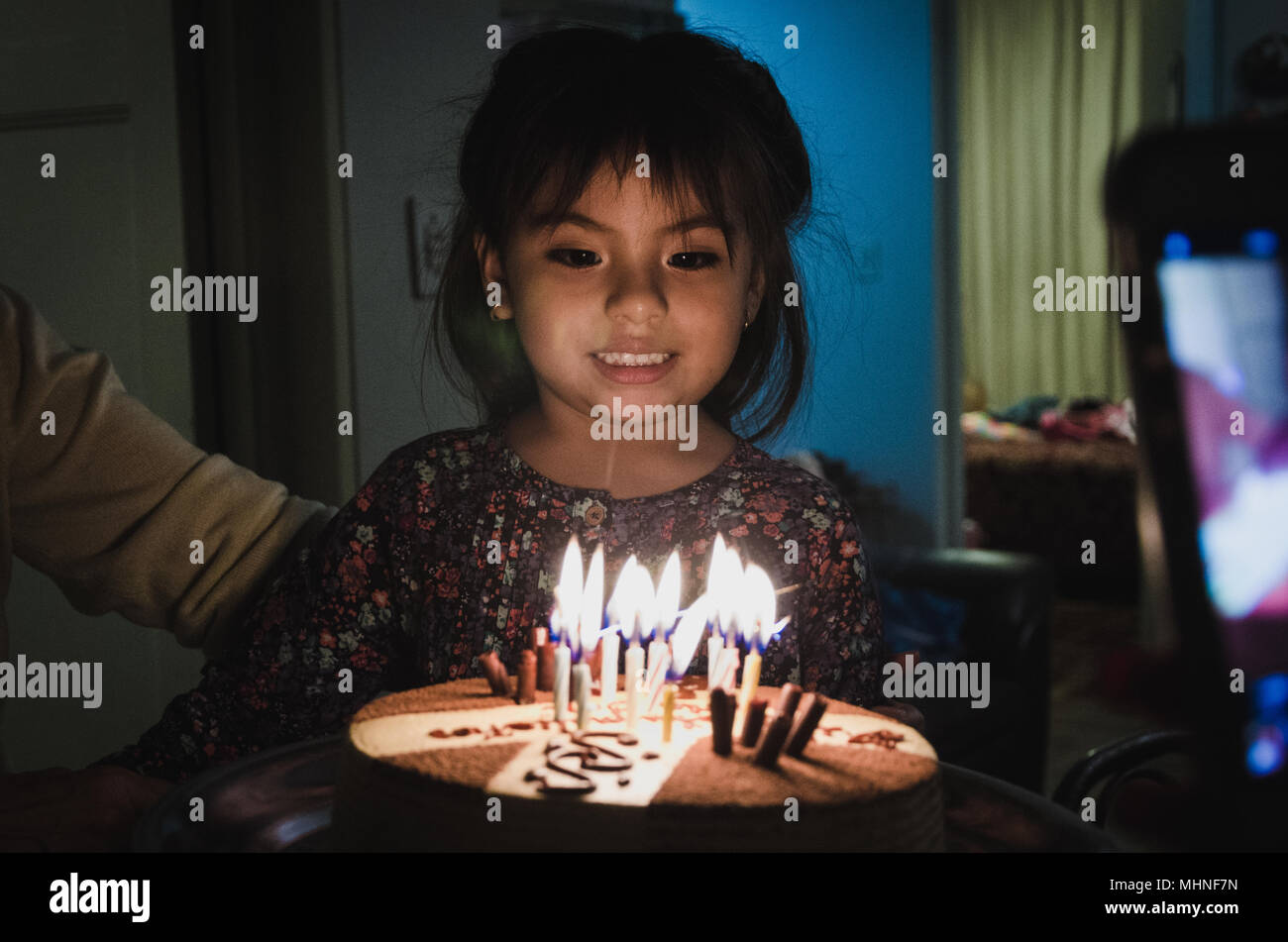 Cake with candles in front of an excited girl - Stock Image