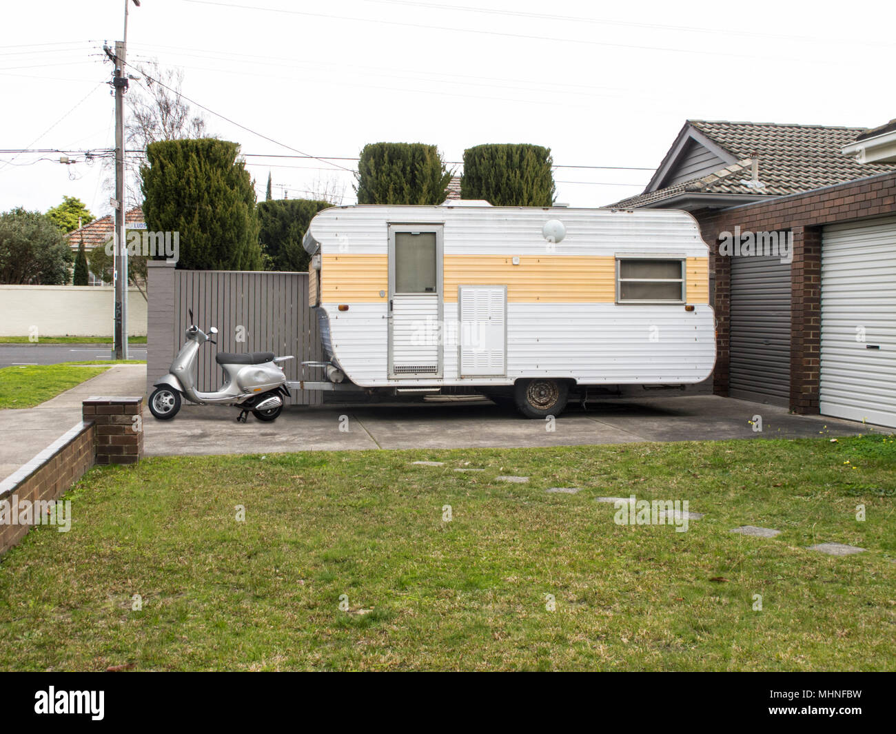 A fun picture of a scooter placed in front of a caravan. - Stock Image