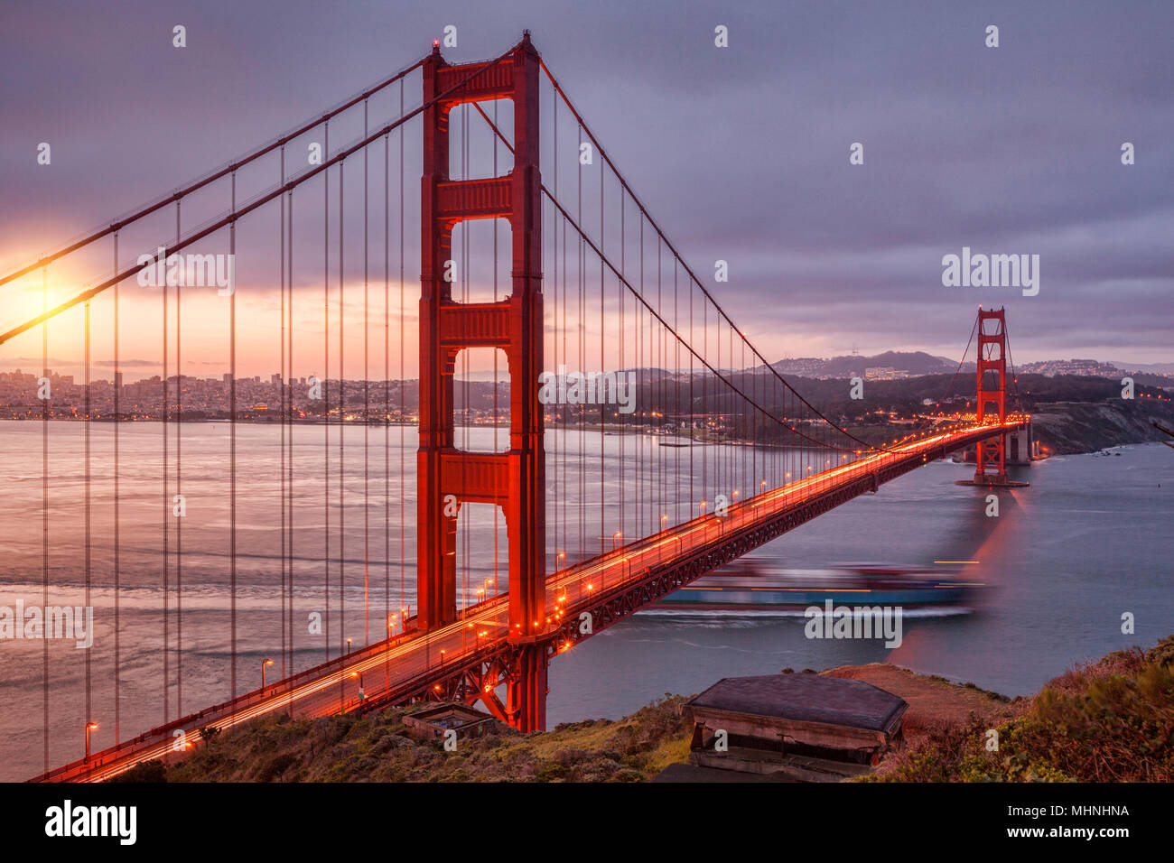 The Golden Gate Bridge, San Francisco, from Battery Spencer at dawn, with traffic on the bridge and a container ship sailing out of the Bay. - Stock Image