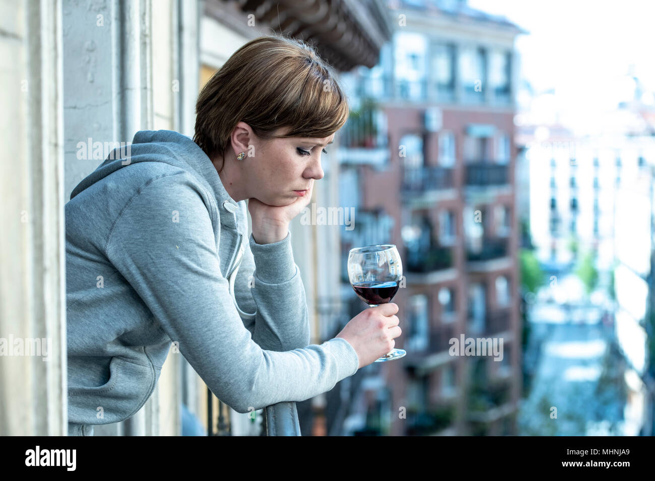 Beautiful red haired caucasian woman suffering from depression holding a glass of wine on a balcony at home. Staring out feeling sad, pain and grief.  - Stock Image
