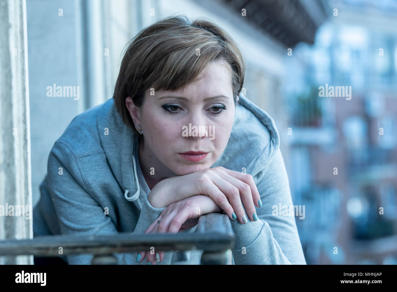 young beautiful unhappy lonely woman suffering from depression staring hopeless and worried on the balcony at home. having feelings of failure, dissat - Stock Image