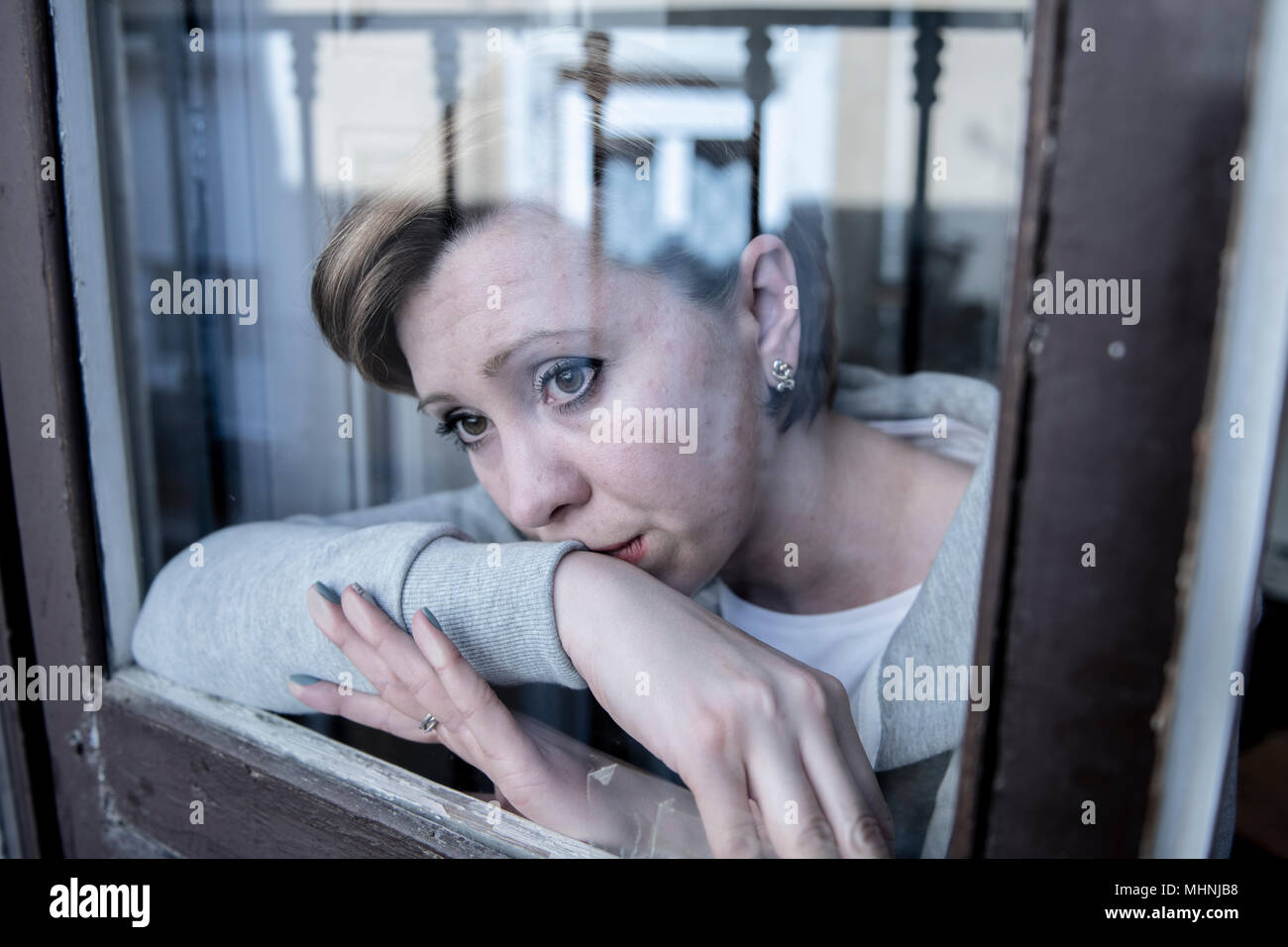 young beautiful depressed unhappy caucasian woman looking worried and sad through the window at home. feeling worthless and in pain. closeup. Depressi - Stock Image