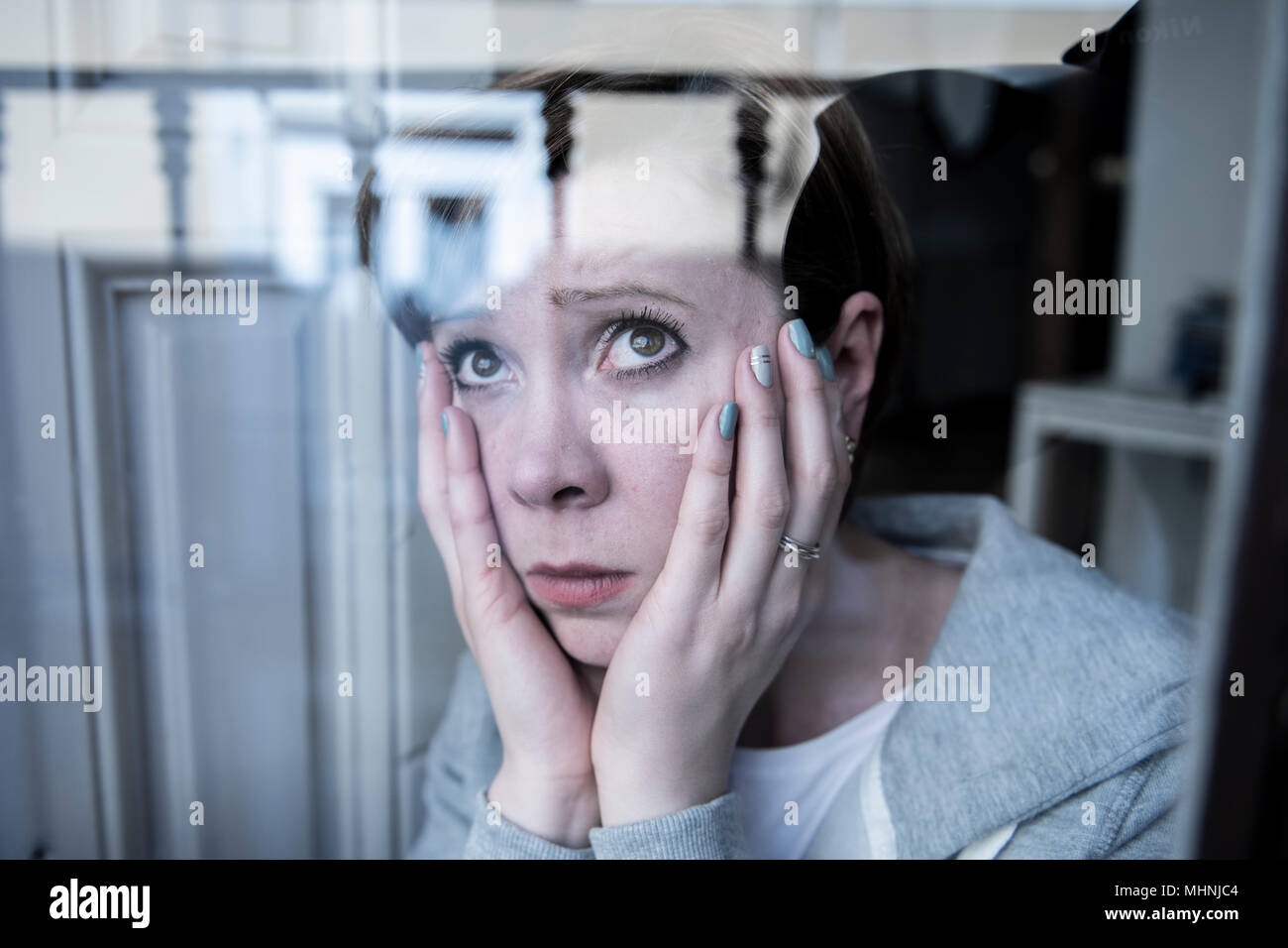 young beautiful depressed unhappy caucasian woman looking worried and sad through the window at home. feeling worthless and in pain. closeup. Depressi Stock Photo