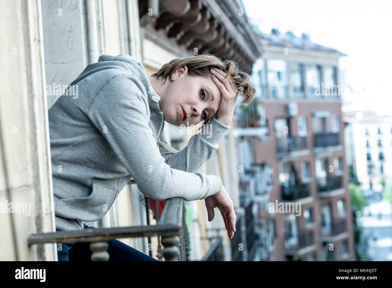 young attractive unhappy caucasian woman with depression and anxiety feeling miserable and hopeless on home balcony. Urban background. Mental health a - Stock Image