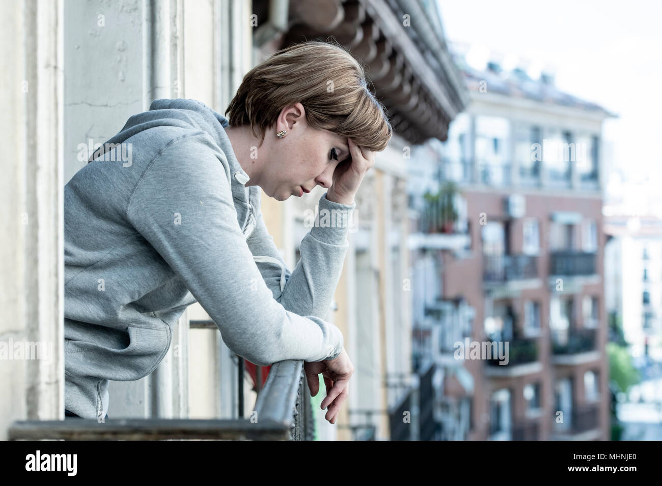 young attractive unhappy depressed lonely woman looking down hopeless on the balcony at home. having feelings of frustration, dissatisfaction, anxiety - Stock Image