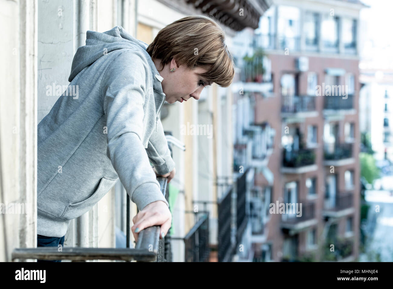 young beautiful depressed lonely woman with depression and anxiety feeling miserable and hopeless looking down the street on the balcony at home. In d - Stock Image