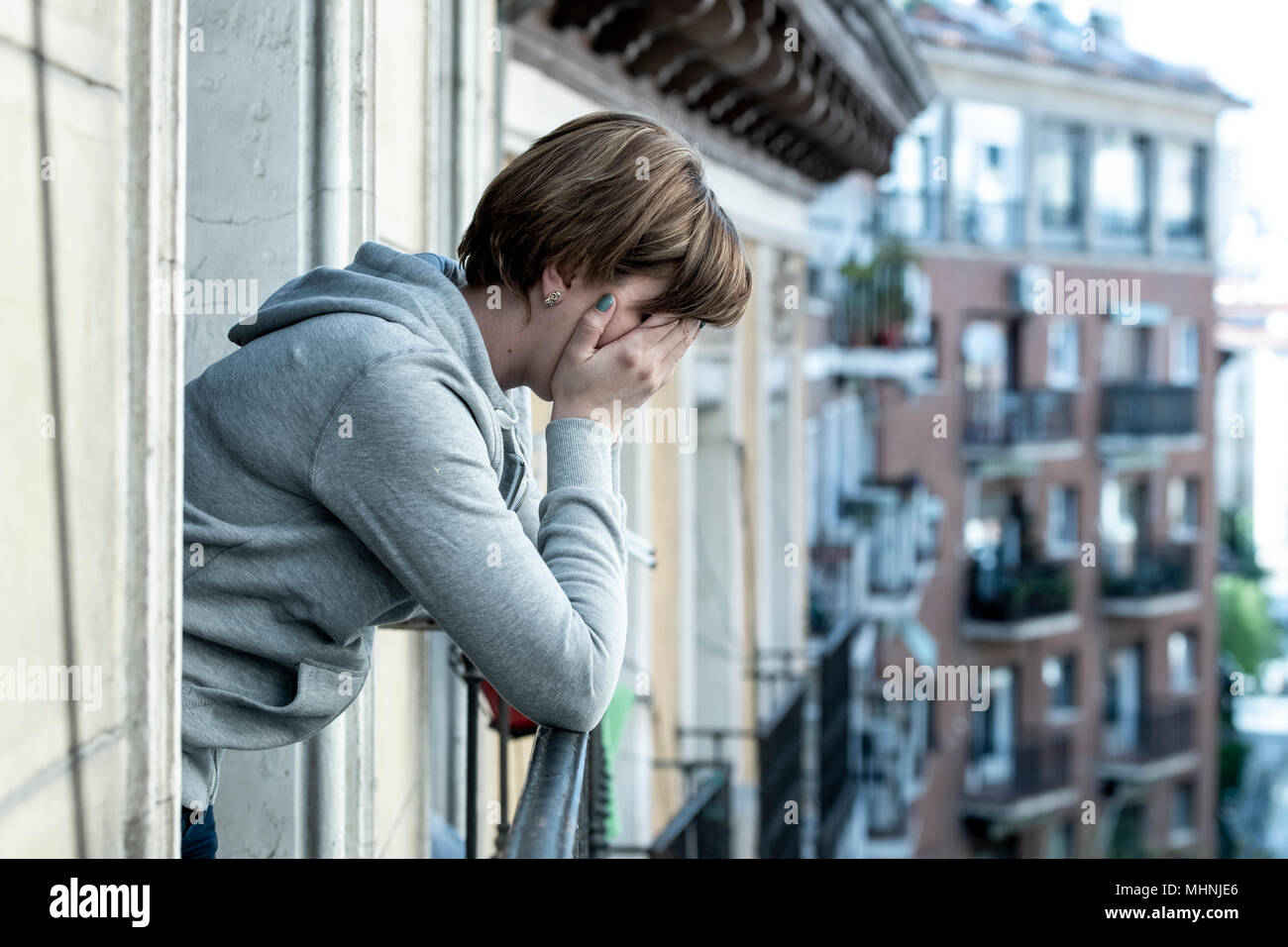 young attractive unhappy suicidal caucasian woman suffering from depression feeling desperate, isolated, worthless on home balcony. Hand on her face w - Stock Image