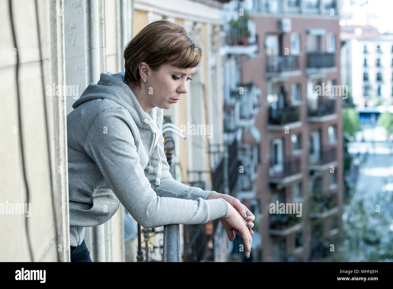 young beautiful, unhappy depressed lonely woman staring hopeless and worried on the balcony at home. having feelings of failure, dissatisfaction. Adul - Stock Image