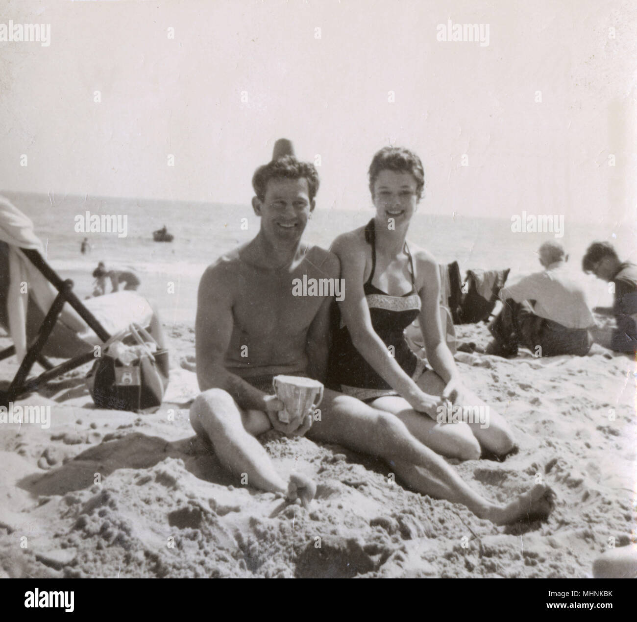 Couple on the beach at Bournemouth - early 1960s. They are fooling about - the sandy contents of his small plastic beach bucket have been deposited on is head!     Date: 1961 - Stock Image