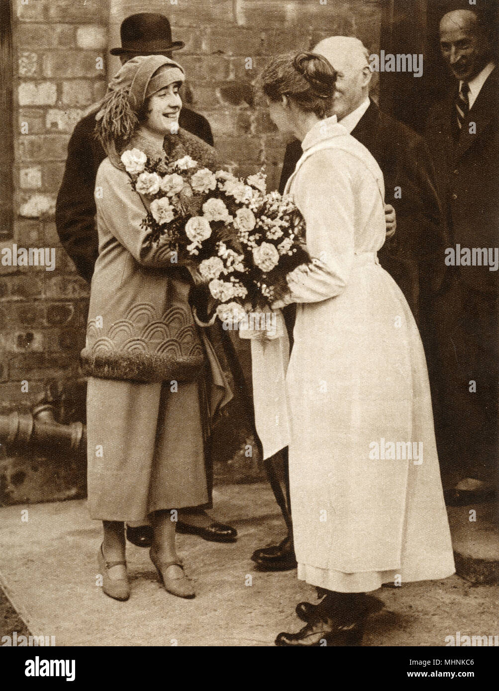 Elizabeth Bowes-Lyon (1900-2002) (later Elizabeth, The Queen Mother) visiting the McVitie & Price factory in Edinburgh, Scotland, the company tasked with making the wedding cake for her forthcoming marriage to Albert, Duke of York (1895-1952) (later King George VI). After seeing all the processes of biscuit and cake making, Lady Elizabeth was presented with a fine bouquet of flowers by the workers.     Date: 1923 Stock Photo