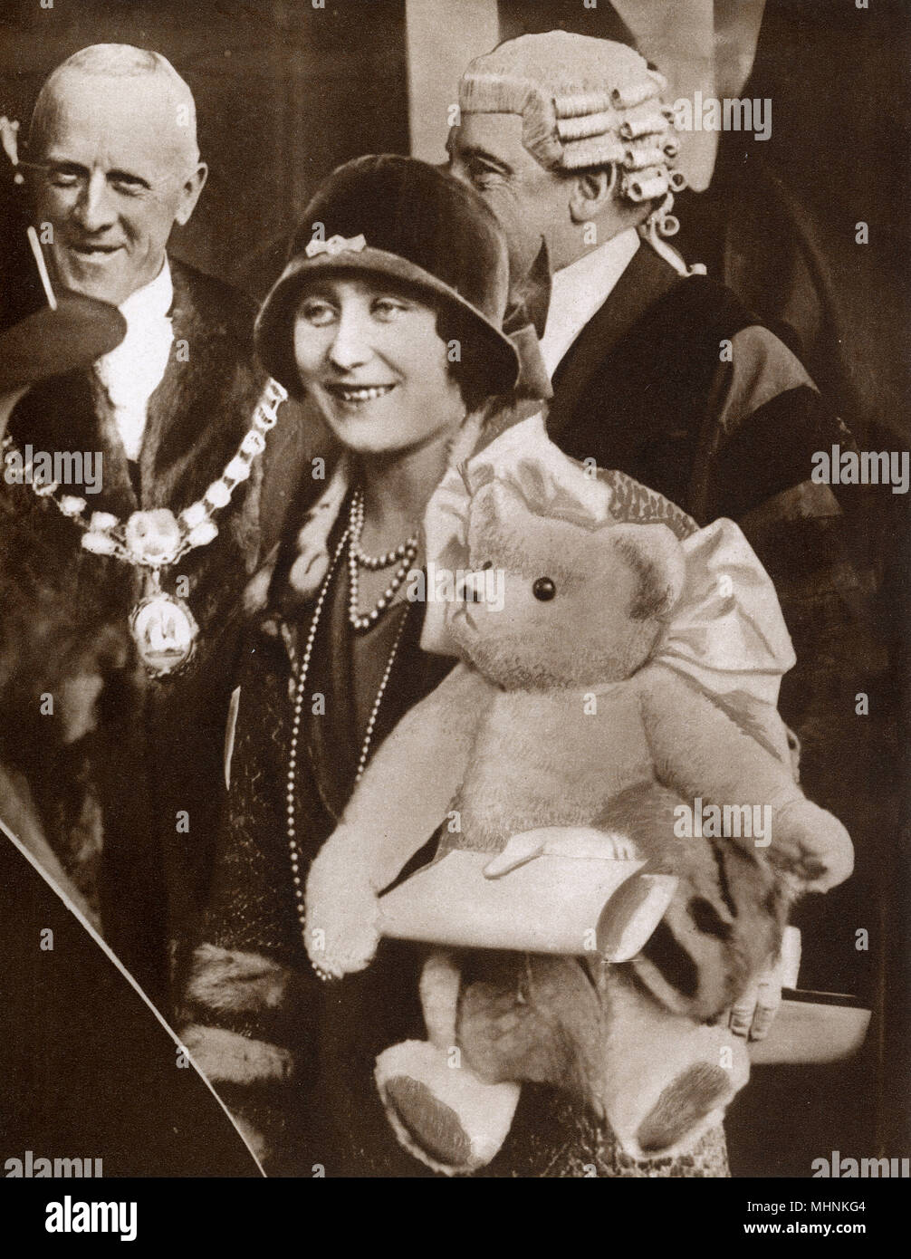 The Duchess of York (1900-2002) (later Elizabeth, the Queen Mother) given a large teddy bear for the infant Princess Elizabeth (the future Queen Elizabeth II) by the small children from the Dr. Barnardo's Home on the occasion of the presentation of a charter granting borough status to Ilford - 21st October, 1926.     Date: 1926 - Stock Image