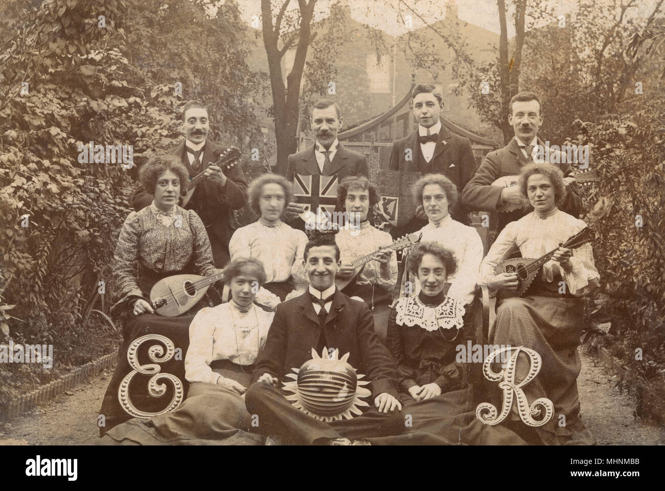 A superb photograph, showing members of a mandolin orchestra (consisting primarily of instruments from the mandolin family of instruments, such as the mandolin, mandola, mandocello and mandobass or mandolone), pictured on 9th August 1902 (when Mandolin orchestras were at the height of their popularity) celebrating the Coronation of king Edward VII. Mandolin orchestras were very popular in the early 20th Century and every city and town and many schools had one. It shows the importance of music as a creative pursuit for the people and communities of this era, and the strength of this should not Stock Photo