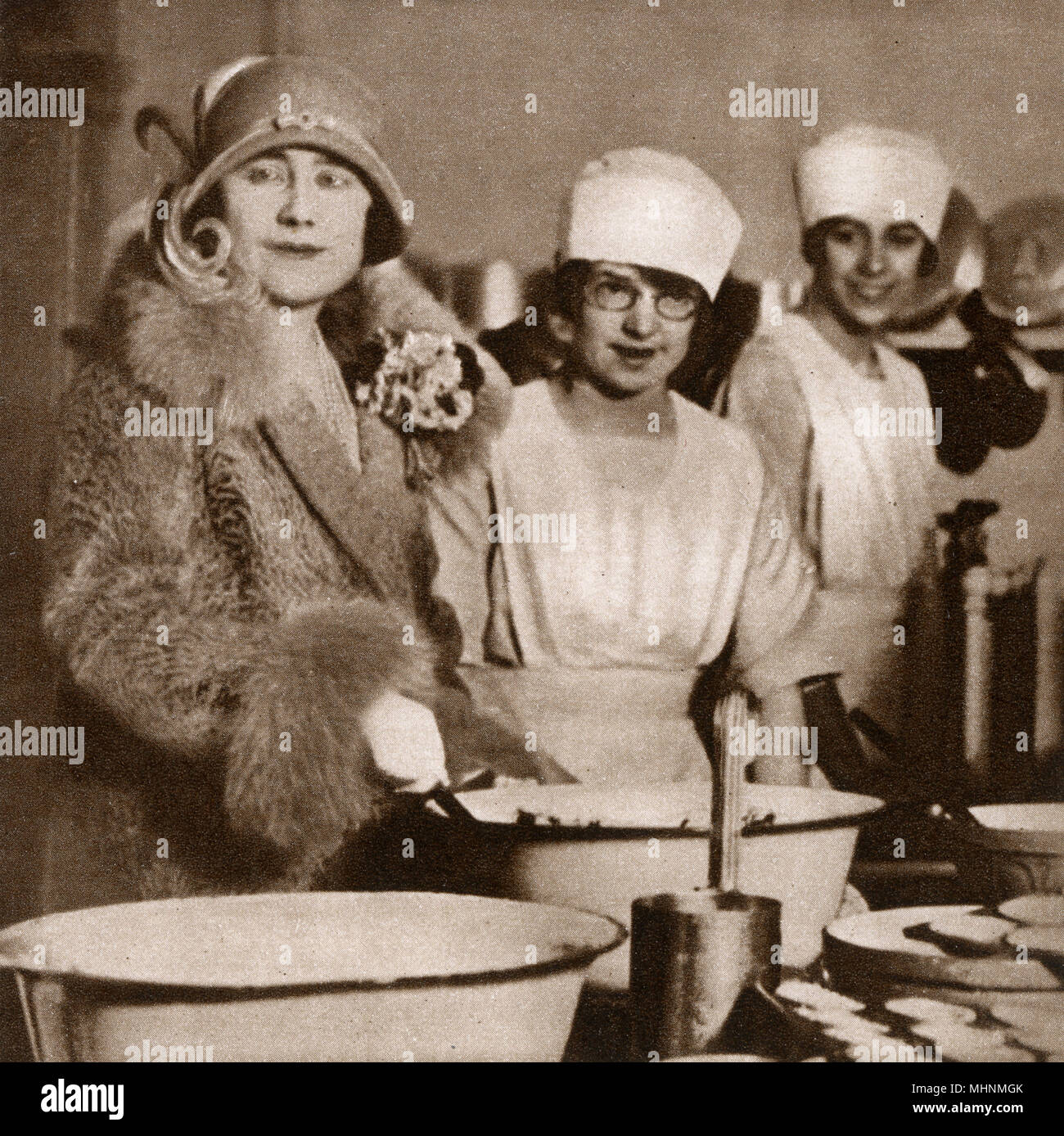 Duchess of York at a Training Hostel, Market Harborough, Leicestershire - part os a scheme fostered jointly by the Imperial and Australian Governments to train girls for domestic service on the Dominion. The girls presented her with an iced cake and in this picture the Duchess is stirring the Christmas pudding.     Date: 1927 - Stock Image