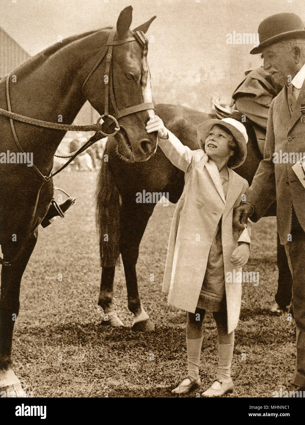 June 15th 1934 - Princess Elizabeth (later Queen Elizabeth II 1926-) meets a champion pony at the Richmond Horse Show (a class of entry she was apparently particularly interested in).     Date: 1934 - Stock Image