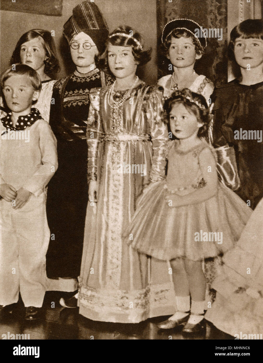 Princess Elizabeth (later Queen Elizabeth II 1926-) and Princess Margaret (1930-2002) pictured at a Fancy Dress Dance given by Viscountess Astor at her house in St. James's Square. Princess Elizabeth dressed in a shimmering Tudor gown is holding the hand of her younger sister, who is dressed as a fairy.     Date: 1934 - Stock Image