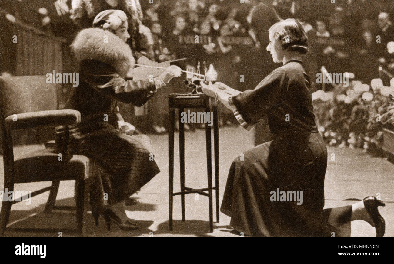 Elizabeth the Duchess of York (later Elizabeth the Queen Mother 1900-2002) lighting lamps at the Toc H League of Helpers Festival and lamplighting Ceremonial at the Royal Albert Hall, London - October 27th 1934. The Duchess lit lamps of 28 new branches including Auckland, Bulawayo and Vancouver. Toc H is an international Christian movement. The name is an abbreviation for Talbot House, 'Toc' signifying the letter T in the signals spelling alphabet used by the British Army in World War I.     Date: 1934 - Stock Image