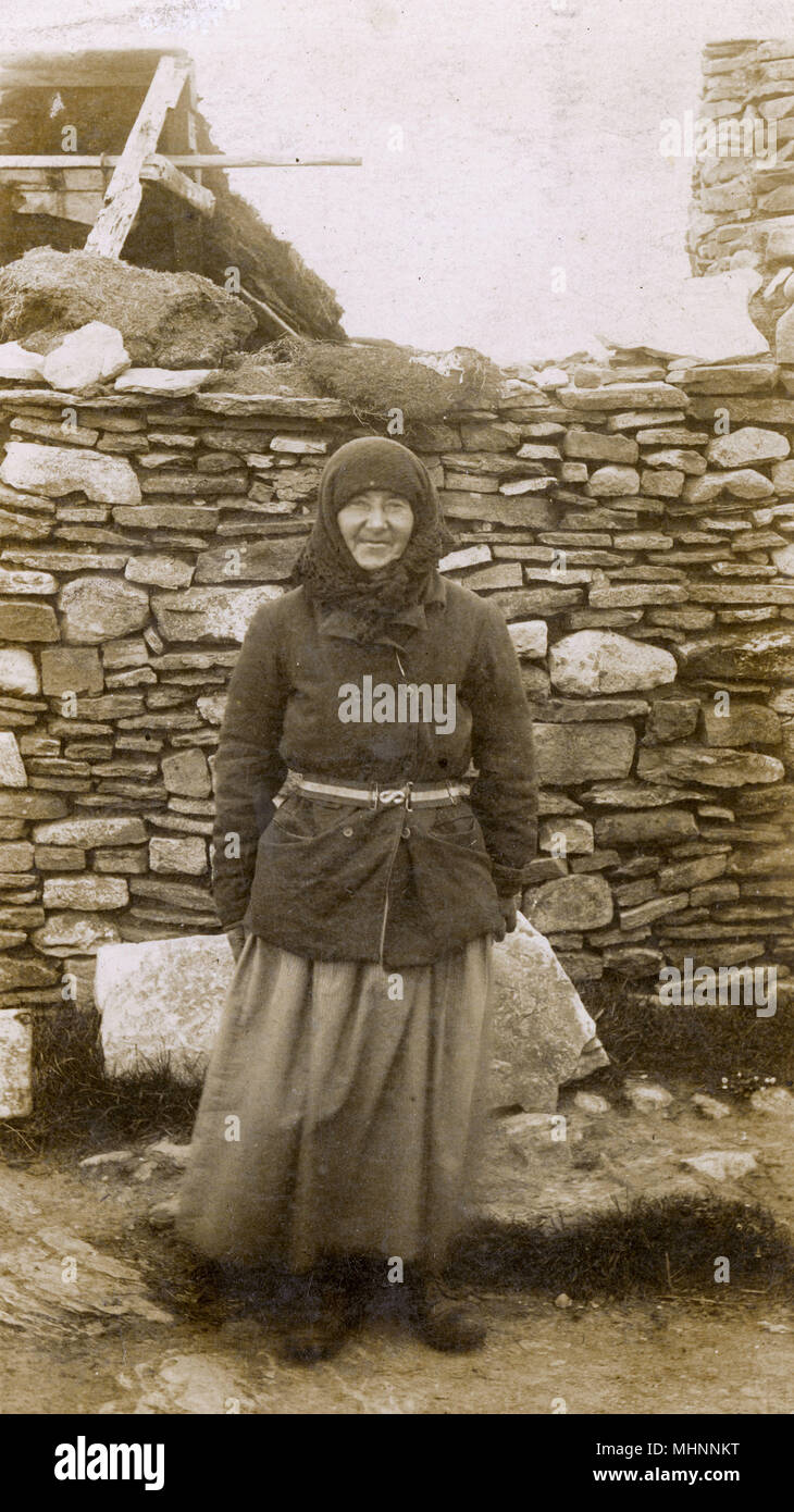 A Local Woman of the Orkney Islands outside her house. Orkney was the site of a Royal Navy base at Scapa Flow, where the sailor who sent this card was stationed (on HMS Royal Arthur) in June 1916, when he sent this card.      Date: circa 1922 - Stock Image