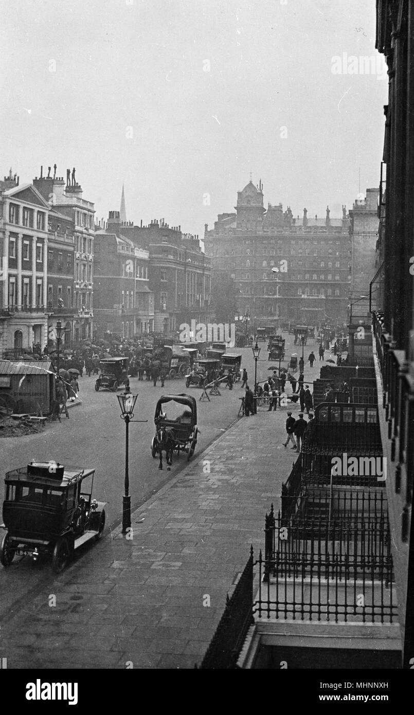 Portland Place, London, with the Langham Hotel at the far end, on a busy day with traffic and crowds of people.      Date: circa 1910s - Stock Image