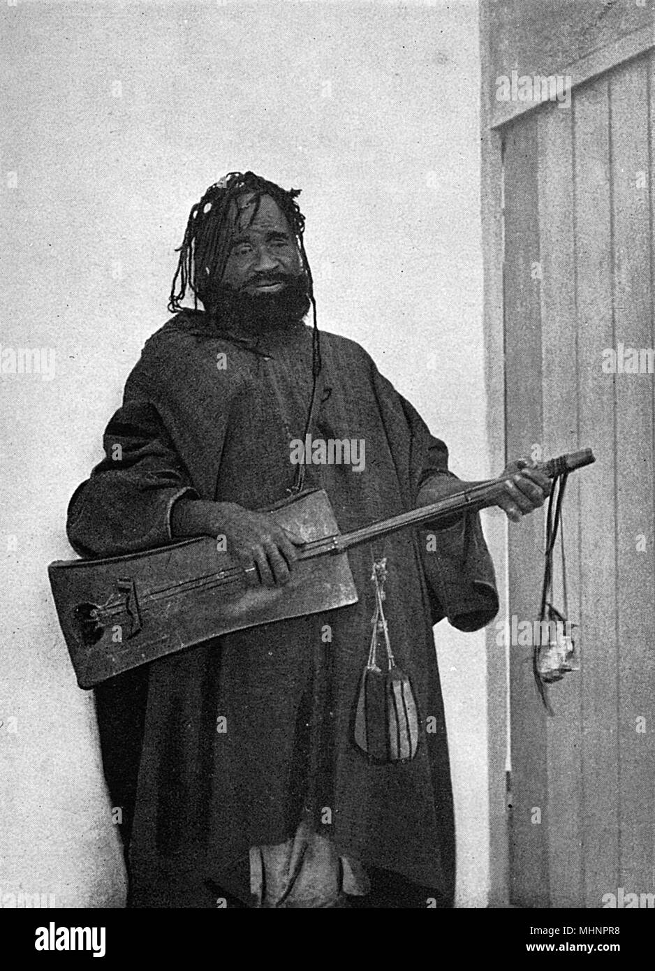 Street Minstrel, Tangier, Morocco, playing a local three-stringed guitar-type instrument., known as a Gimbri.     Date: 1929 - Stock Image