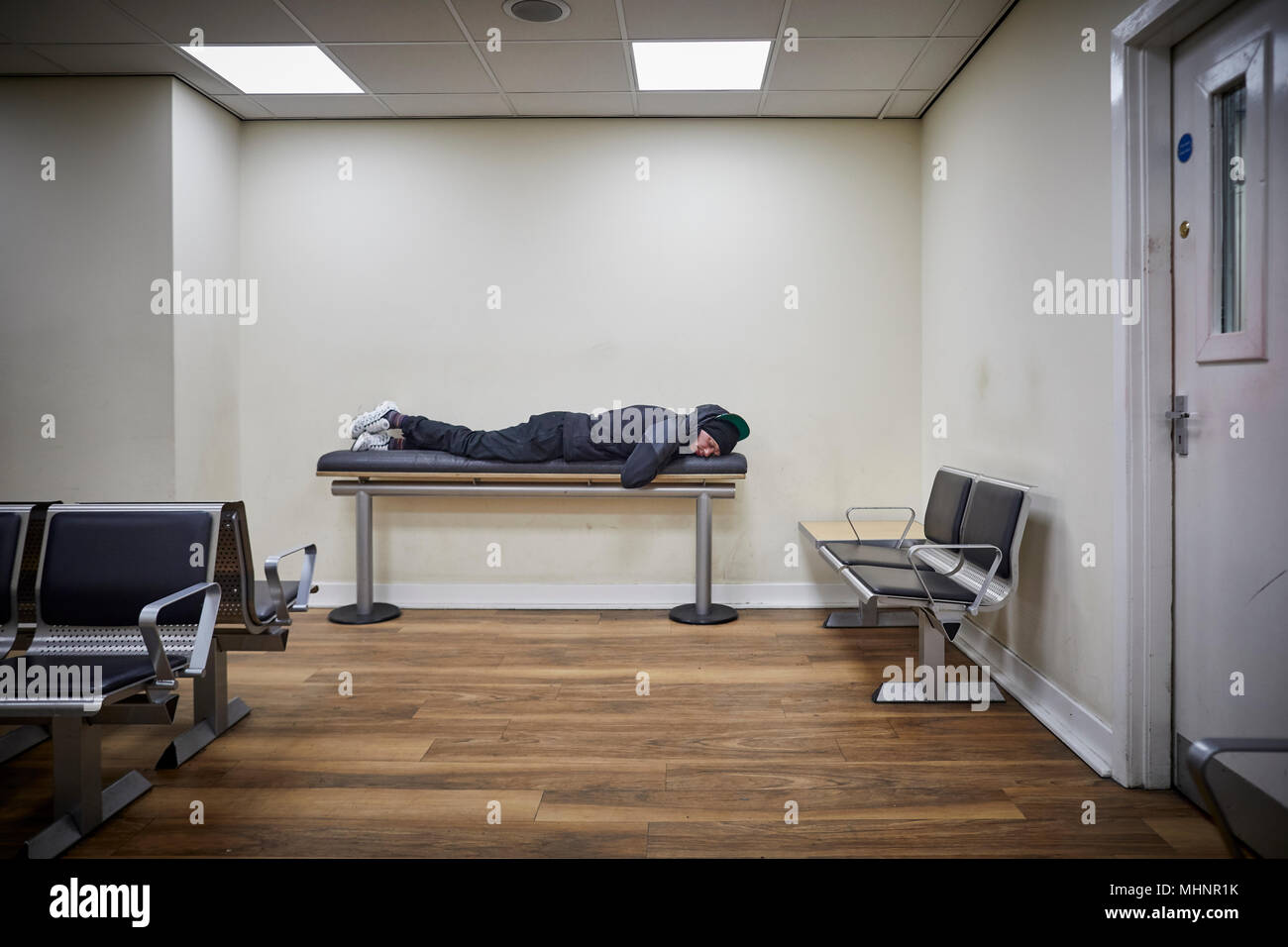 Glasgow in Scotland, Glasgow Central man sleeps on bench in waiting room - Stock Image