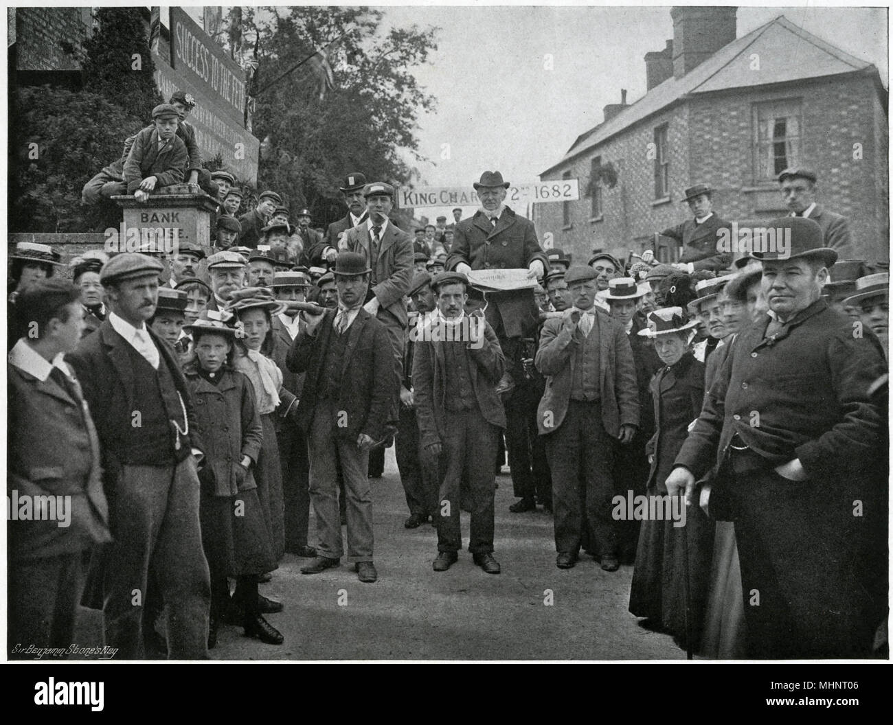 'The Chairman, with the Charter'. Corby Pole Fair, in Northamptonshire taken place every 20 years on Whit-Monday since 1682, in celebration of the charter granted by Elizabeth I exempting local landowners from bridge tolls throughout the Kingdom. Photograph showing here of a procession with band at the head and organisers' leaders seated in chairs attached to poles which are borne on the shoulders of some of the men.      Date: 1902 - Stock Image