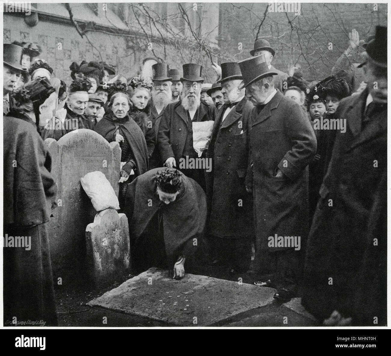 Centuries-old tradition, when twenty-one sixpences were placed upon a flat gravestone in the churchyard at St. Bartholomew in Smithfield, London, on Good Friday morning. Gathered are twenty-one aged widows with the church officials and a few spectators. Photograph showing a widow kneeling and picking up one of the sixpences, on rising she receives a freshly-baked  hot-cross bun from another gentleman, who then assists her to walk over the stone, subsequently each widow is presented with a penny and hot-cross bun the gift from the churchwarden.     Date: 1902 - Stock Image