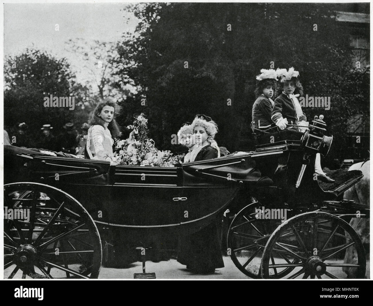 Formerly the Queen was always a scholar at the parish school and chosen by the committee, photograph showing the start of the procession at the Town hall in Knutsford, Cheshire, with bands playing and banners flying the to be crowned  'Queen of the May' and attendants in the carriage waiting to start.     Date: 1902 - Stock Image