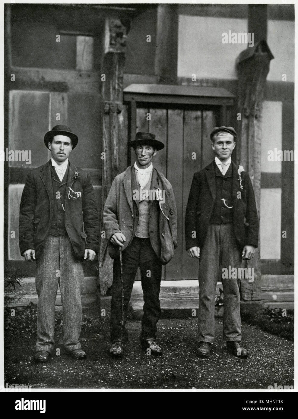 'Standing for Hire', Stratford-upon-Avon, said to be the largest fair in England, regarded by the agricultural class in the district as the chief holiday of the year. Annually in October, farm workers, labourers and servants, would attend the Mop Fair dressed in their Sunday best clothes and carrying an item signifying their trade  in their buttonhole. Grooms carry a bit of straw, shepherds a twist of wool, carters a length of whipcord and servants with no particular skills would carry a mop head - hence the phrase Mop Fair, the custom was general at hiring fair.     Date: 1899 - Stock Image
