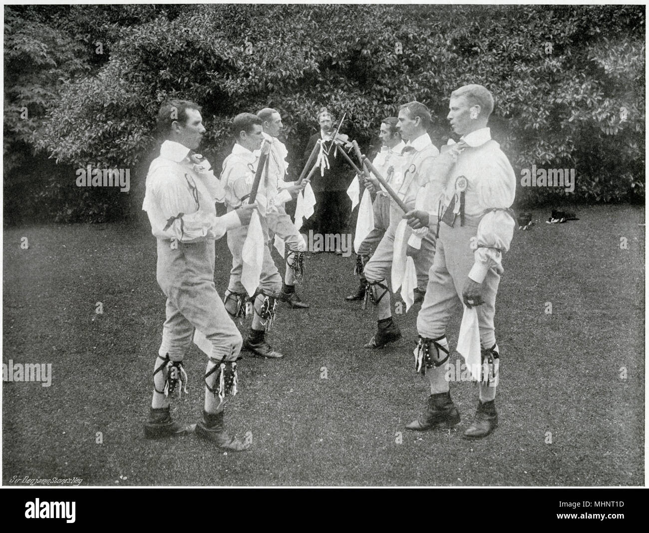 'Dancing the Hay', English morris dancers in traditional clothing at Stratford-upon-Avon, Mop Fair. Most probable derivation of the word 'hay' is from the French haie, a hedge, the dancers standing in two rows, being linked to hedges. But the hay was danced in a circle as well as a line.     Date: 1899 - Stock Image