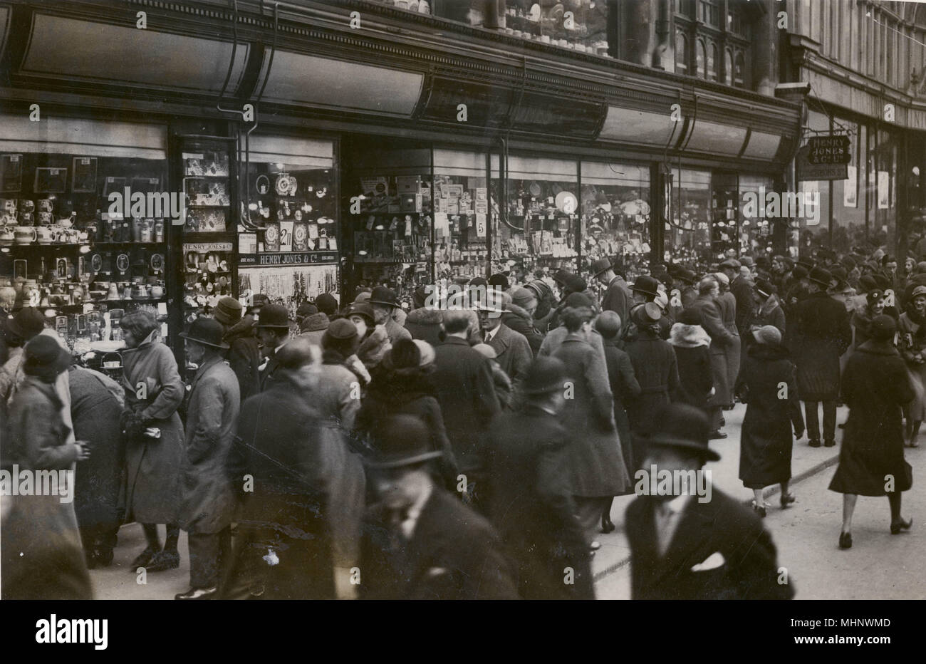 Crowds of passers by browsing at the shops as they go past 'Henry Jones' merchandise. The shop next-door is closed propley due to the Great Depression of the 1930s.     Date: 1933 - Stock Image