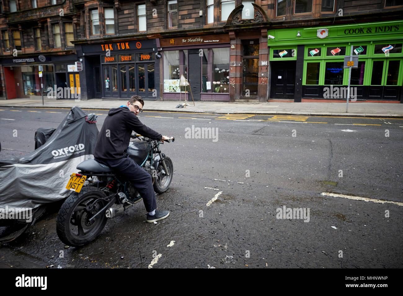 Glasgow in Scotland,   Sauchiehall Street young resident starting his motorbike - Stock Image