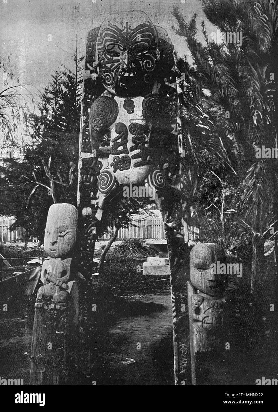 A specimen of Maori wood carving at Rotorua, in the Hot Lake district of the North Island of New Zealand, representing the god Tiki.     Date: circa 1900 - Stock Image