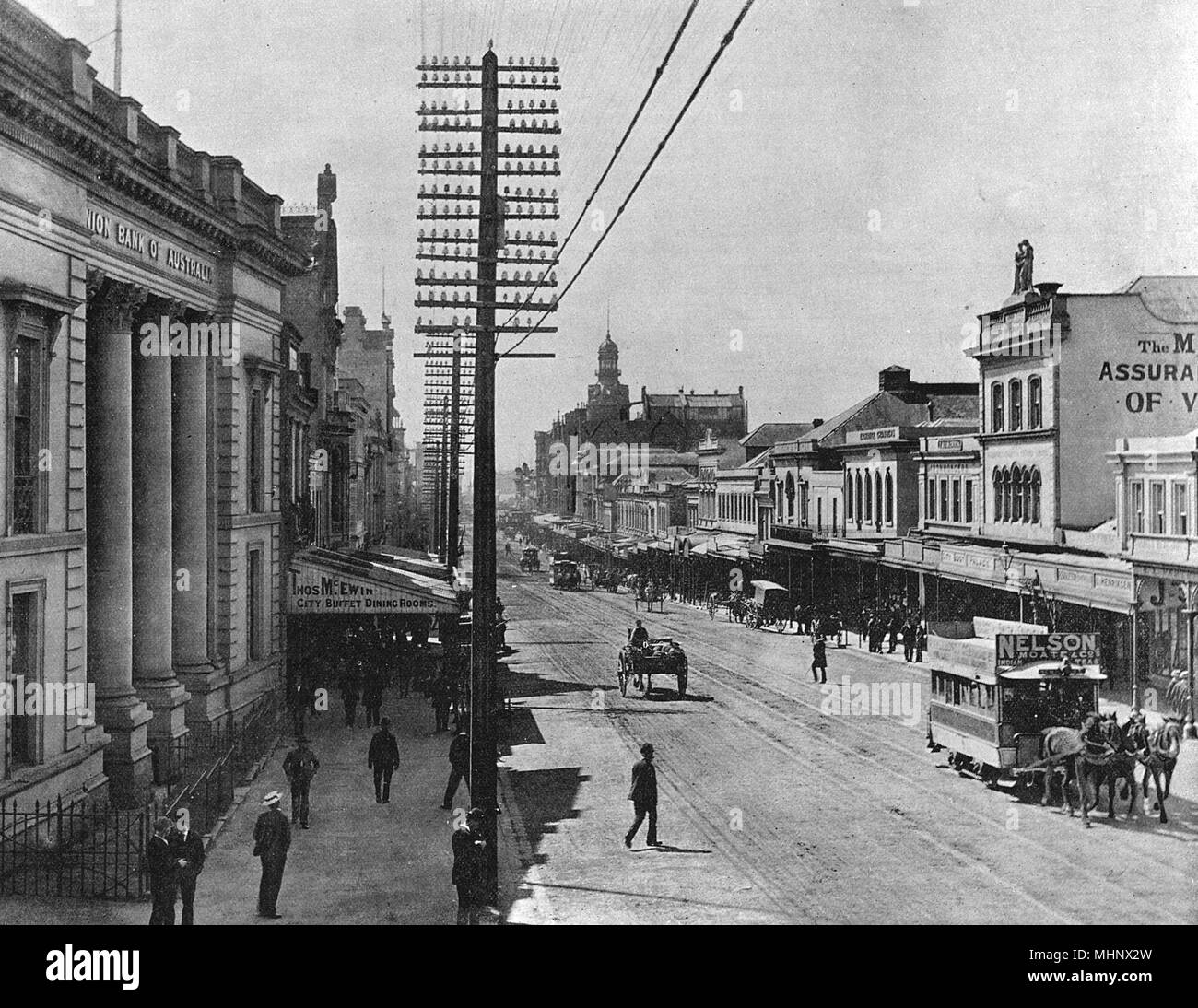 Queen Street, the main street of Auckland, North Island, New Zealand, with banks, office buildings, shops and clubs.      Date: circa 1900 - Stock Image