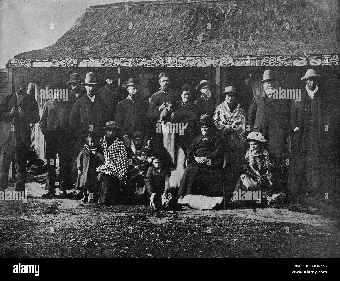 Refugees from the Maori village of Wairoa, North Island, New Zealand, following the eruption of Mount Tarawera in 1886, when their village was buried in mud and lava. Seen here in a group photo in Ohinemutu, outside a whare (hut).      Date: circa late 1880s - Stock Image