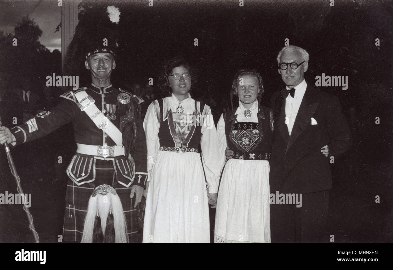 Scotsman in dress uniform (with 14/15 star and war medals) with two girls wearing white dresses with embroidered bodices, and a man in evening dress.      Date: circa 1920s - Stock Image