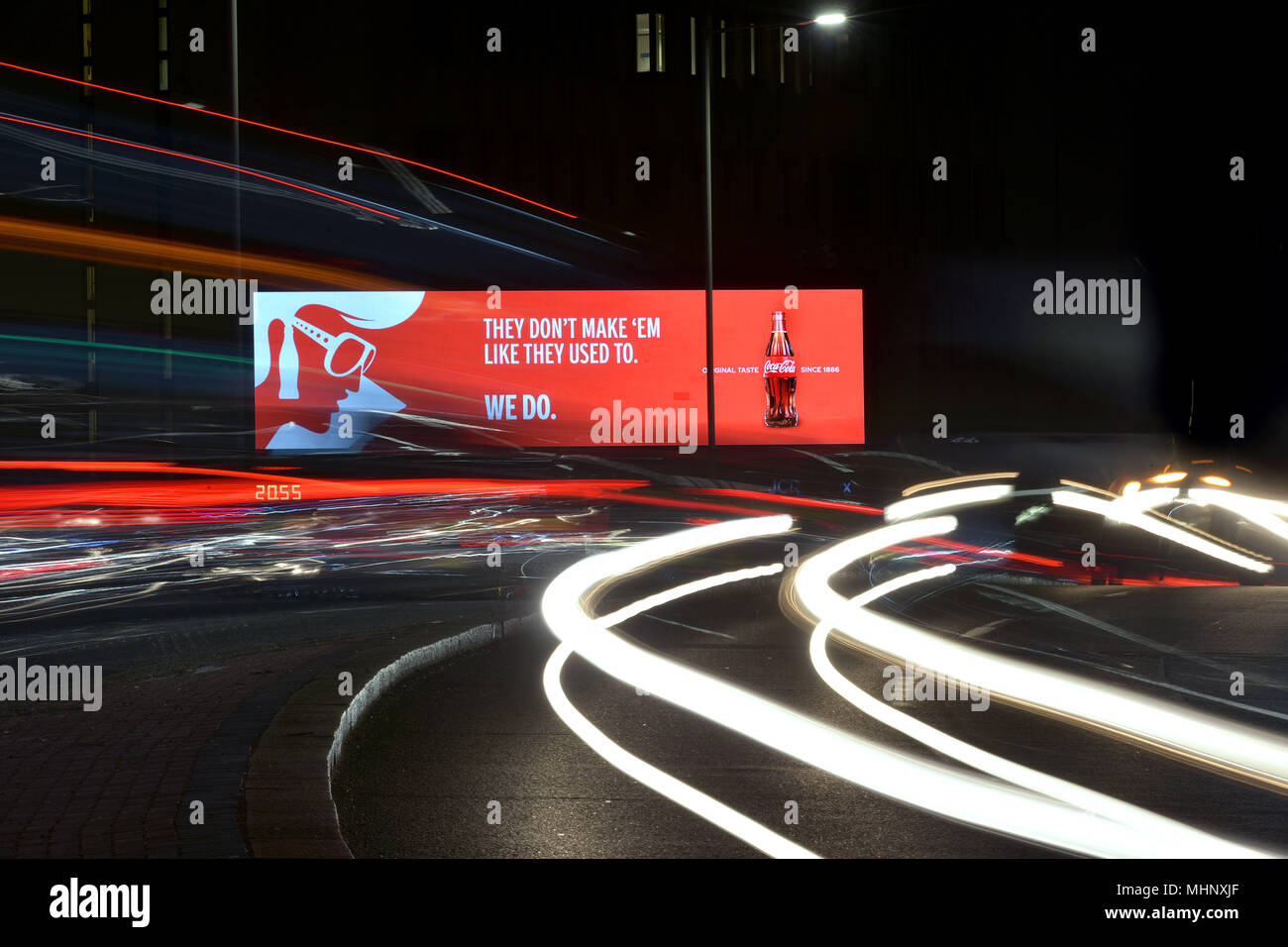 Digital advertising hoardings promoting coca cola on the Talgarth Road, Fulham  in West London, UK. Coca cola have not changed their drink recipe dspi - Stock Image