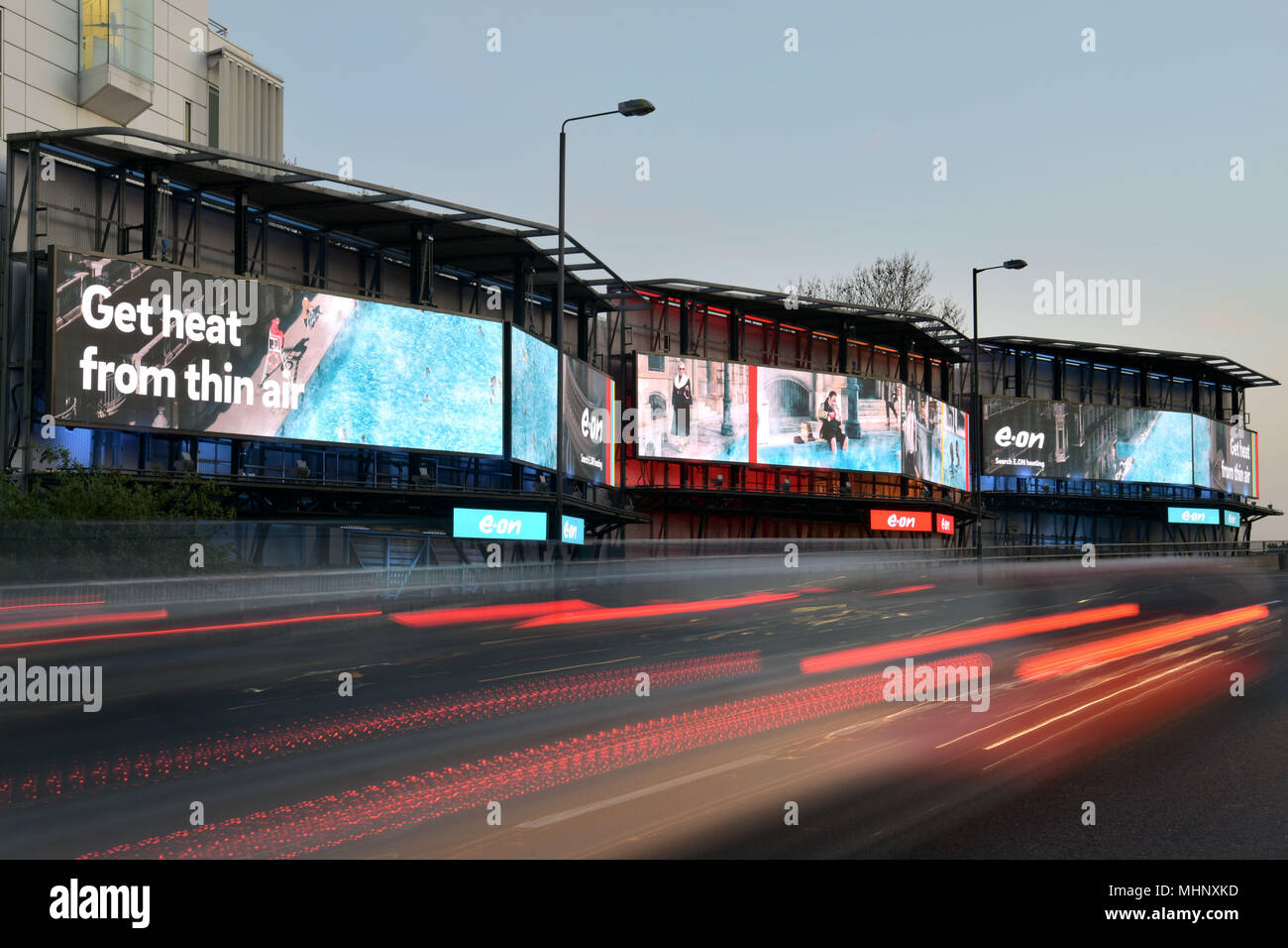 Digital advertising hoardings promoting the domestic energy company E-on on the Talgarth Road, Fulham  in West London, UK. - Stock Image