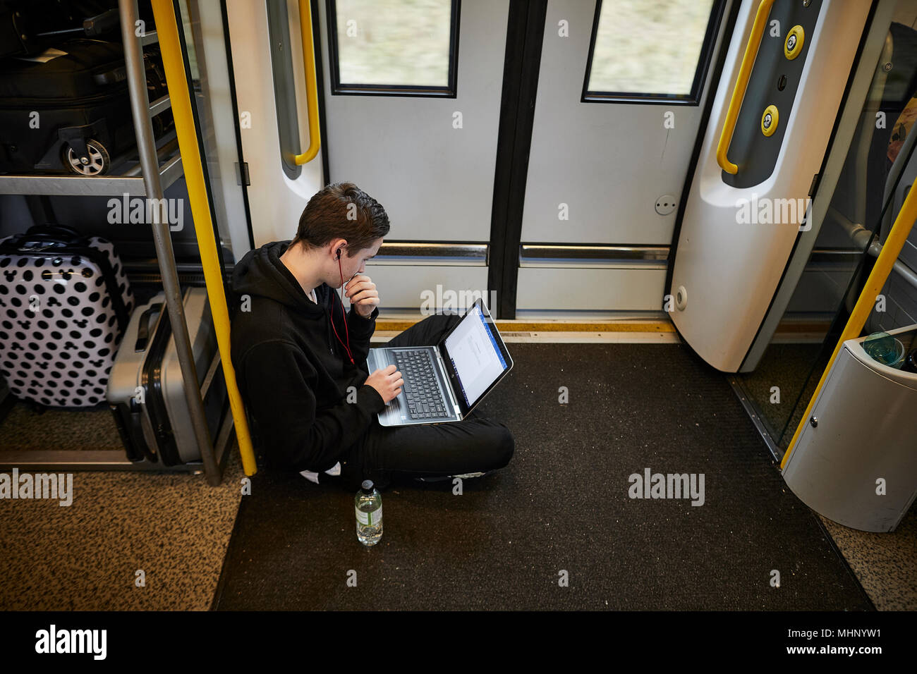 Glasgow in Scotland,   Glasgow Central to Manchester Airport Transpennie Express train with passenger standing, young man working int he doorway - Stock Image
