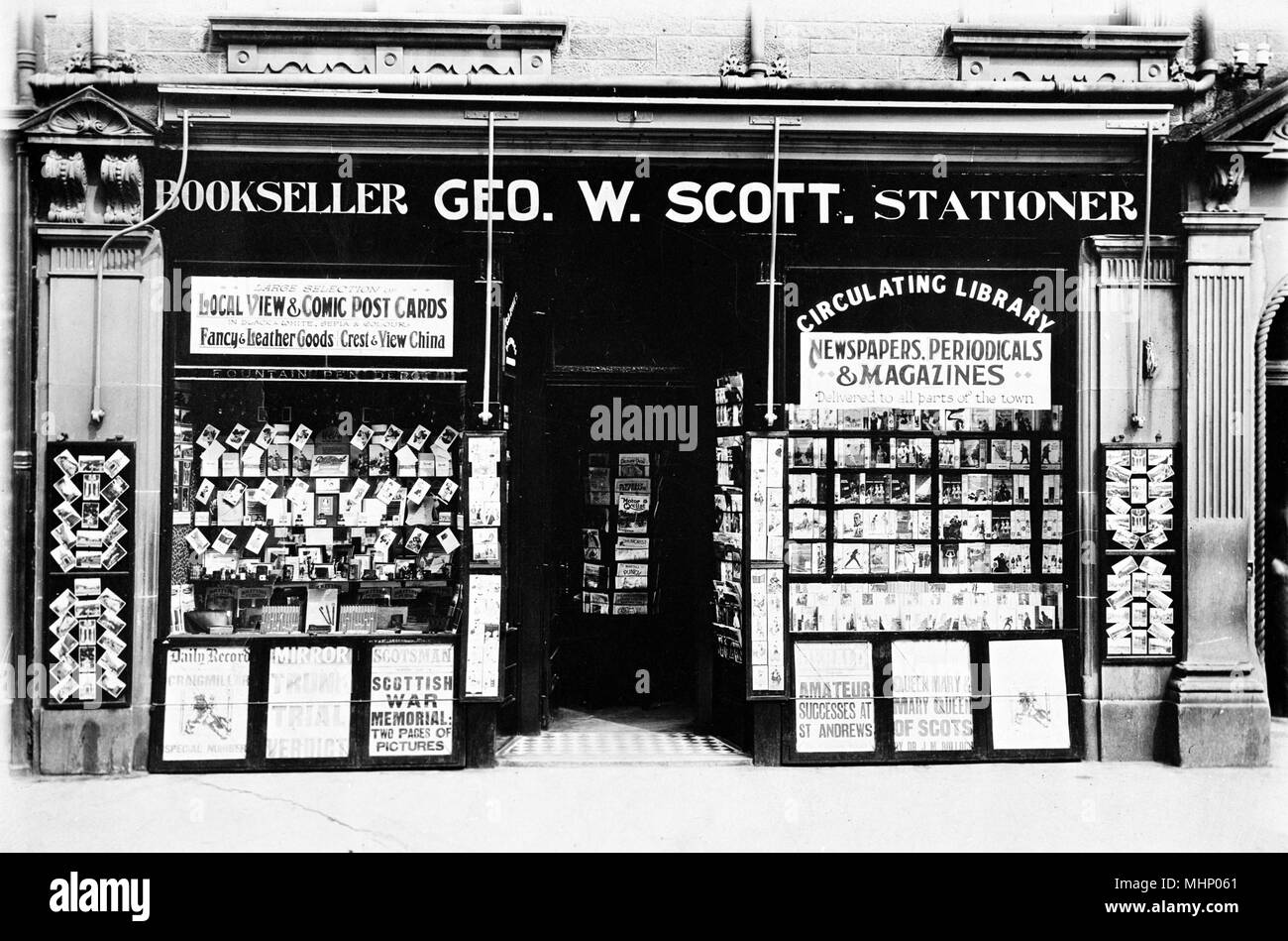 Premises of Geo W Scott, Bookseller and Stationer, somewhere in Scotland, with newspaper headlines on display outside, postcards in the left window and circulating library books in the right window.      Date: circa 1930s - Stock Image