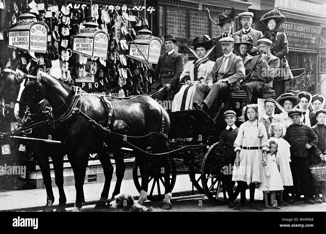 People on a horse-drawn carriage outside Oliver's Boot and Shoe Warehouse, Ilfracombe, Devon, taken on 18 August 1909.      Date: 1909 - Stock Image
