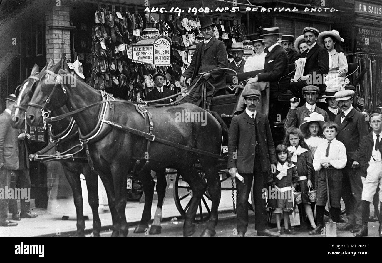 People on a horse-drawn carriage outside Oliver's Boot and Shoe Warehouse,Ilfracombe, Devon, taken on 19 August 1908.     Date: 1908 - Stock Image