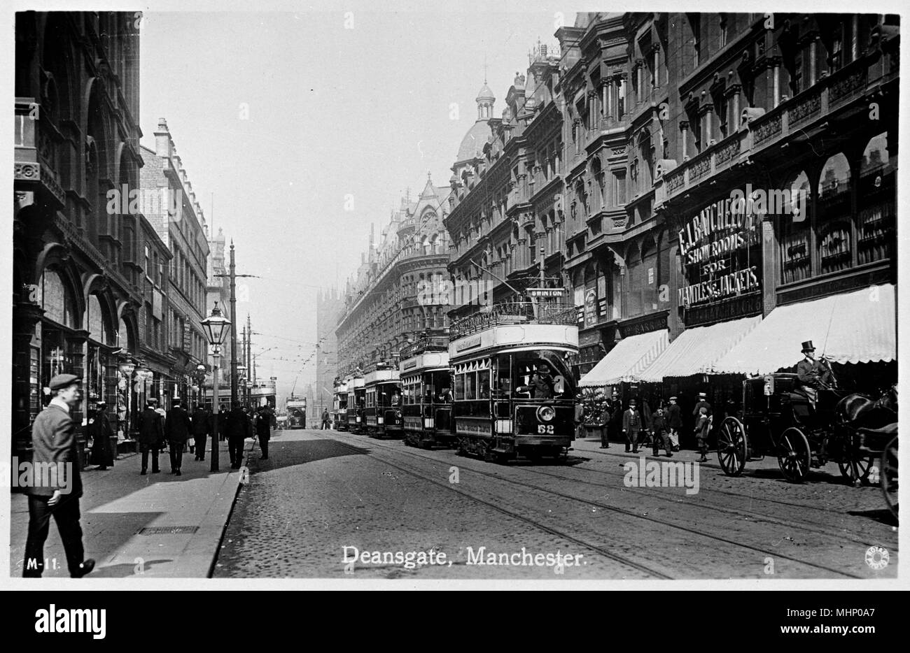 Deansgate, Manchester, with a line of trams in the middle, and the Batchelor Showrooms on the right.      Date: circa 1920s - Stock Image