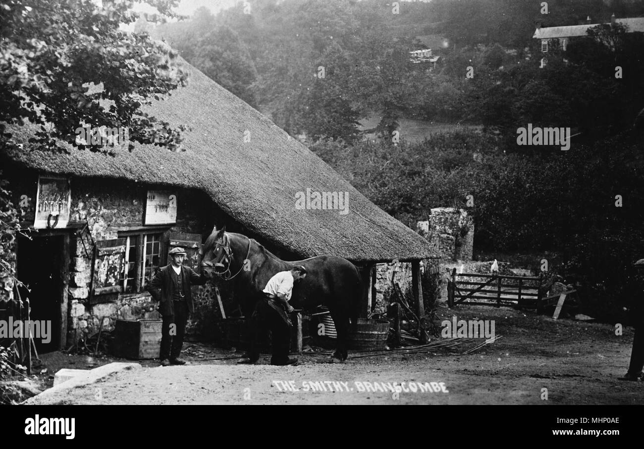 Old Smithy at Branscombe, near Sidmouth, Devon, with a horse having a hoof inspected.      Date: circa 1910s - Stock Image
