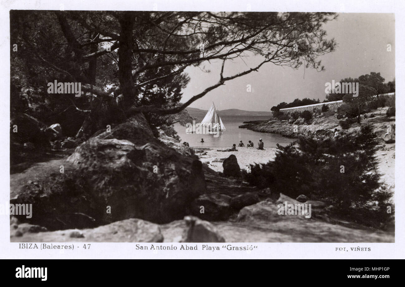Grassio beach, San Antonio (Sant Antoni de Portmany), Ibiza, Balearic Islands, Spain, with a sailing boat on the water.     Date: circa 1950s - Stock Image