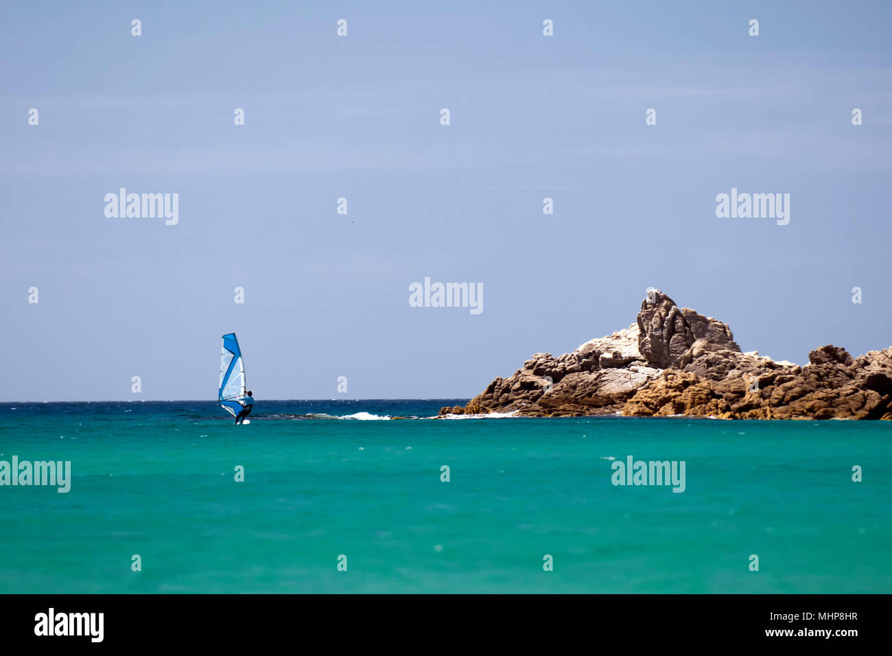 A windsurf in the tourquoise blue sea in Sardinia Italy - Stock Image