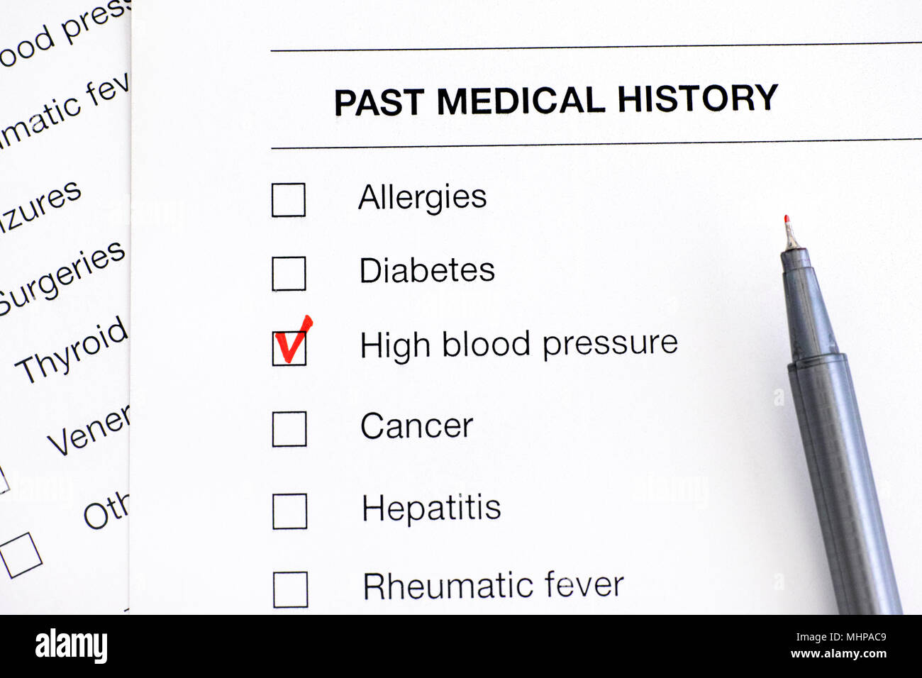 Past medical history questionary with ticked High Blood Pressure and pen. Close-up. - Stock Image