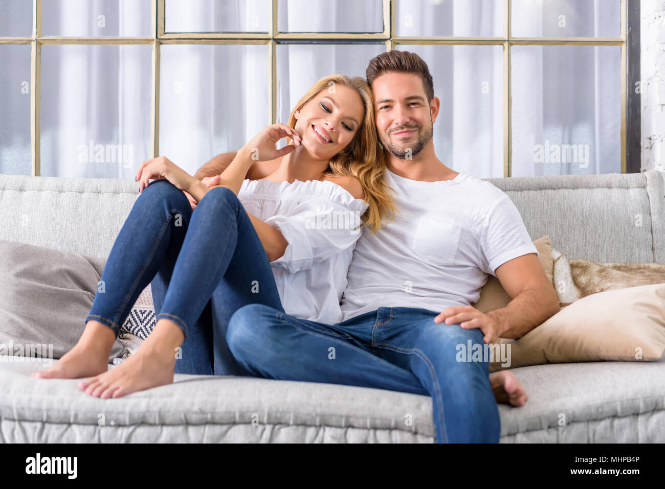 A Beautiful Young Couple Sitting On The Sofa And Cuddling ...